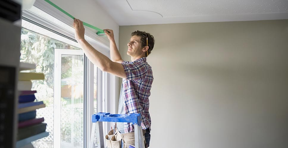 Man refreshes his living room space by measuring his windows for new curtains.