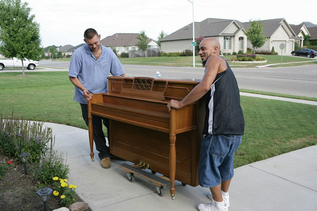 Professional movers help transport a valuable piano into a new home.