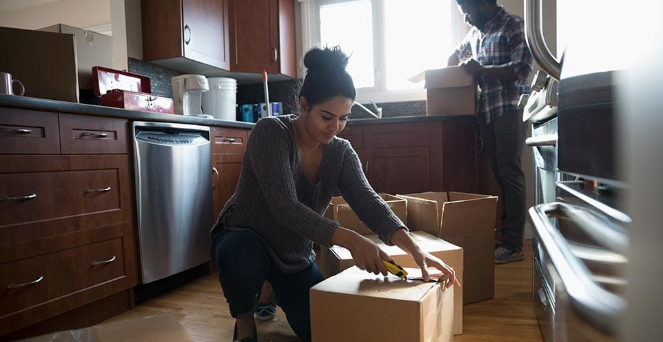 a young woman in the kitchen cutting open a moving box