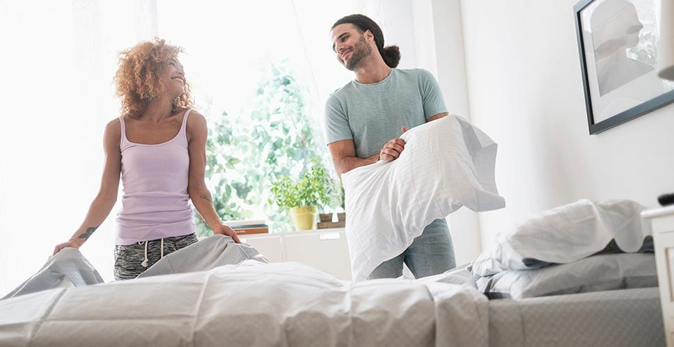 a young couple in their bedroom making their bed
