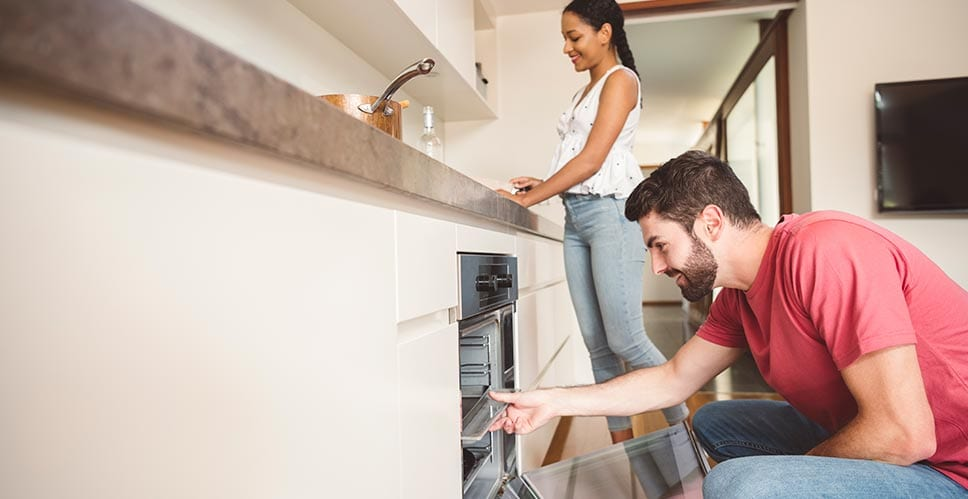 Young couple cooks in their kitchen with few worries about their home appraisal process.