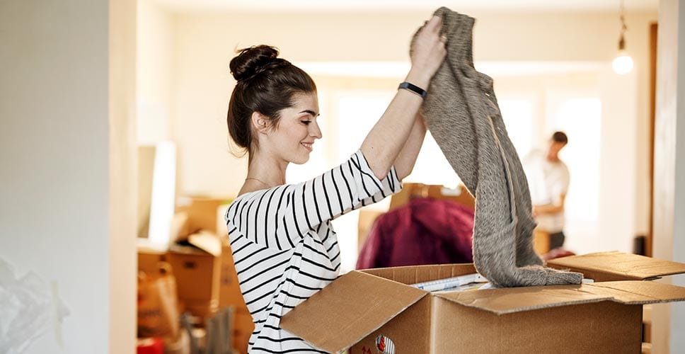 a young girl packing a sweater into a moving box