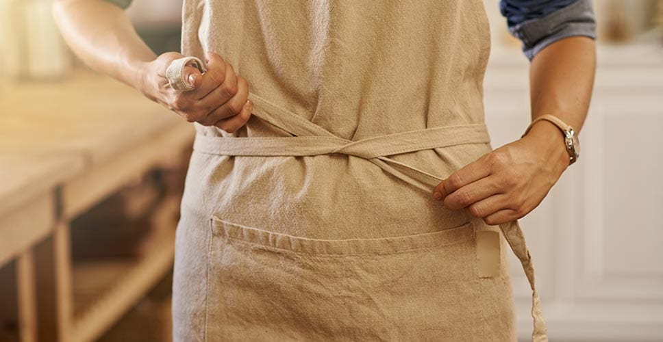 A woman putting on his apron — a product worth investing in for move day.