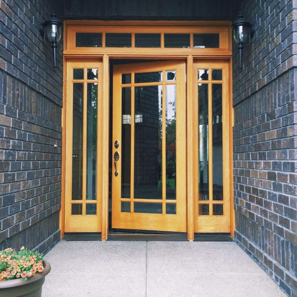 Exterior home entryway with brick walls and wood doors with windows
