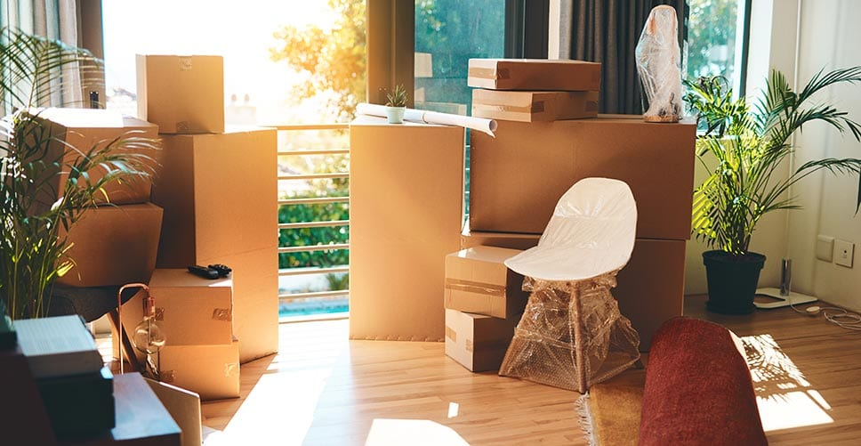 A living room filled with half-packed boxes shows the need for the help of a voice assistant.
