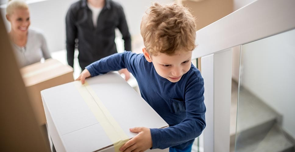 small boy carrying a box