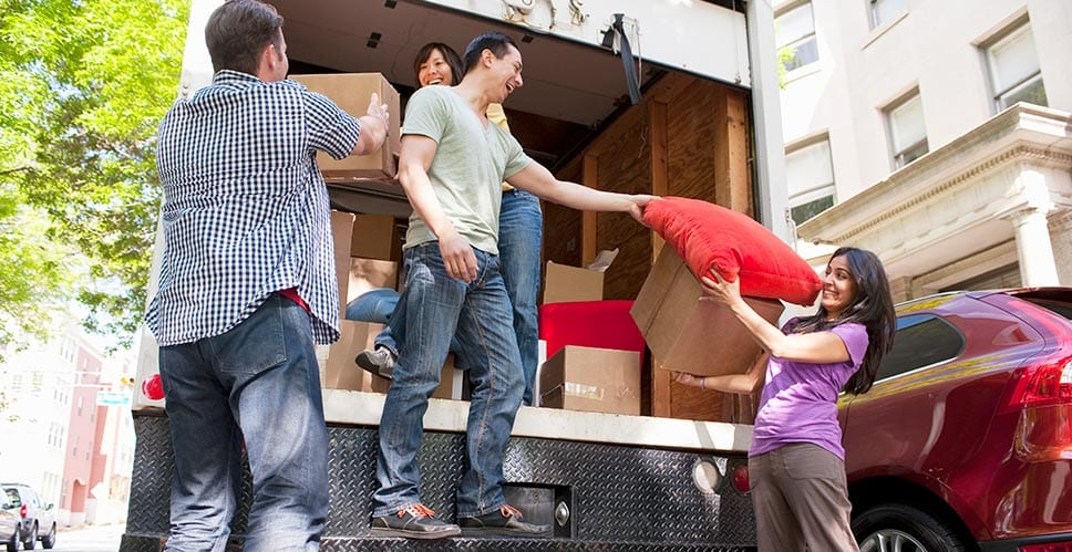 a group of young adults loading a moving truck