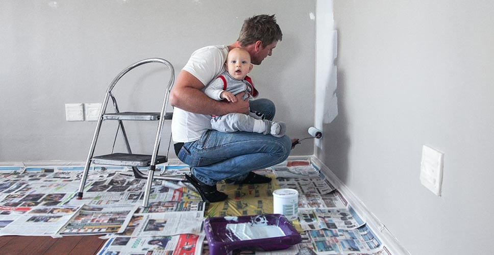 man holding a baby while painting a room wall in a house
