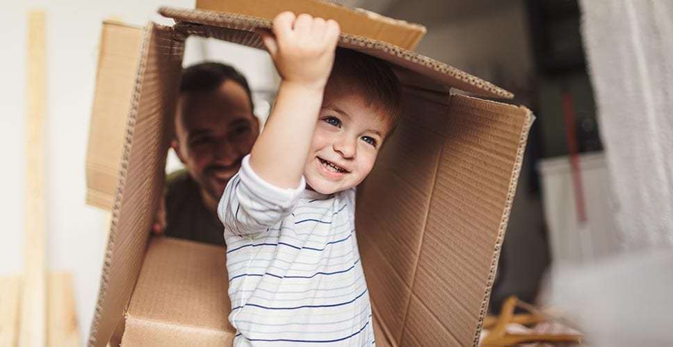 toddler playing in an empty box shows that moving with an infant can be challenging