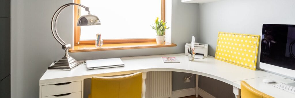 White wooden corner desk with office supplies