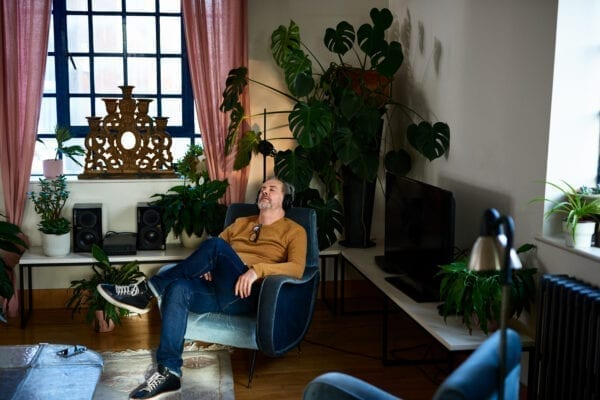Man sitting in armchair wearing headphones in living room, calm, solitude, escapism