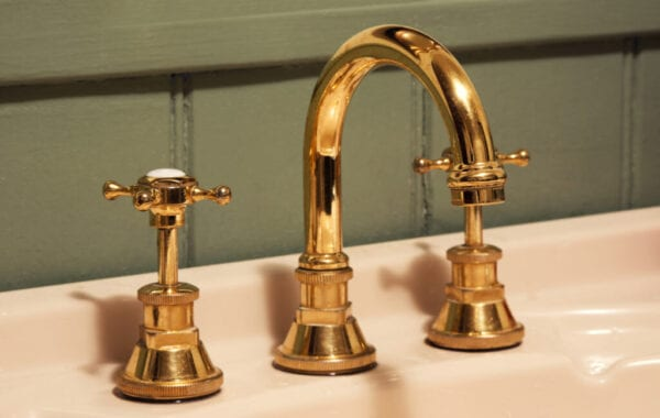 Close-Up Of Gold Tap And Faucet On Sink