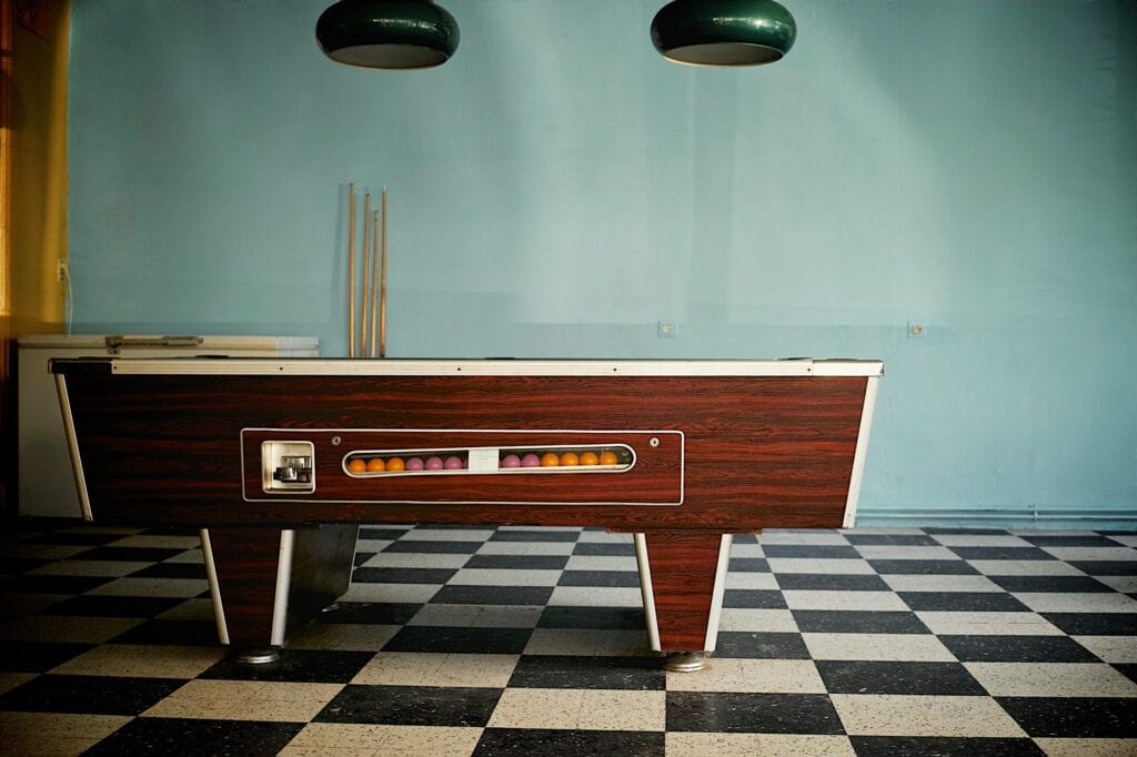 Vintage game room with pool table, with retro lamps and checkerboard floors
