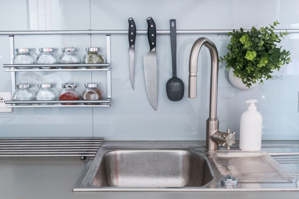 Kitchen sink surrounded by other kitchen utensils and objects