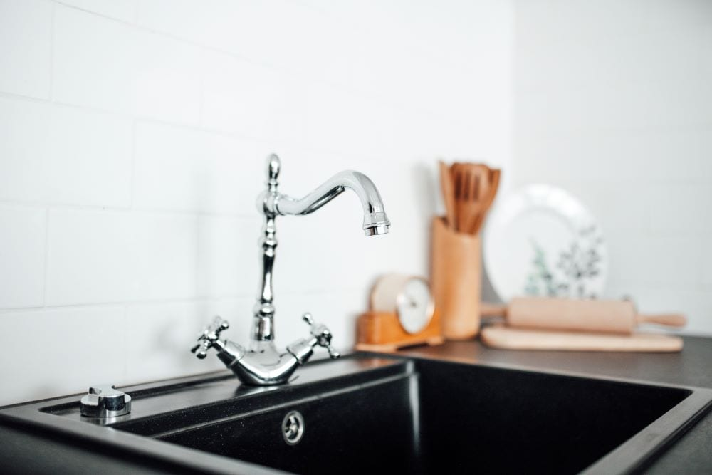 Black kitchen sink with silver faucet