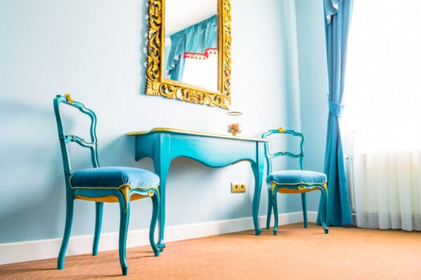 Two blue vintage chairs and a wooden table, next to a wall with a mirror, decorated with yellow floral swirls on its frame. Blue curtains on the side with soft natural light coming in from outside.