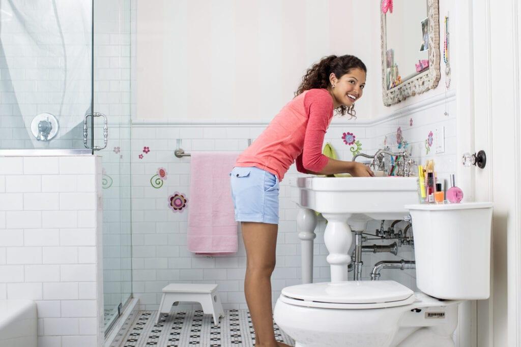 girl in bathroom washing face