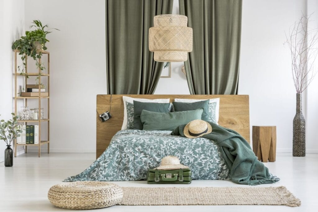 Modern boho style bedroom with green floral bedspread