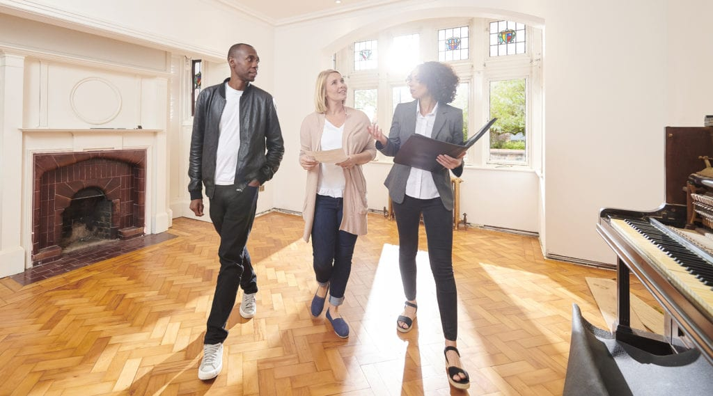 young couple tours first apartment with real estate agent