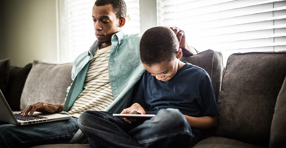 Father and young son sitting on the couch using their laptop and tablet to access the internet.