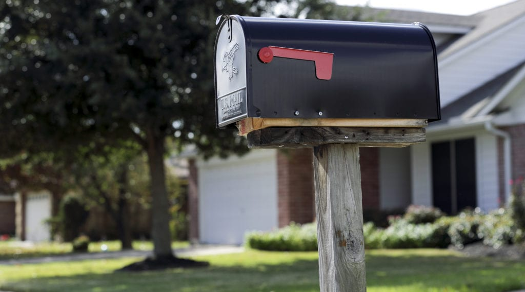 A mail black mail box in front of a new home.