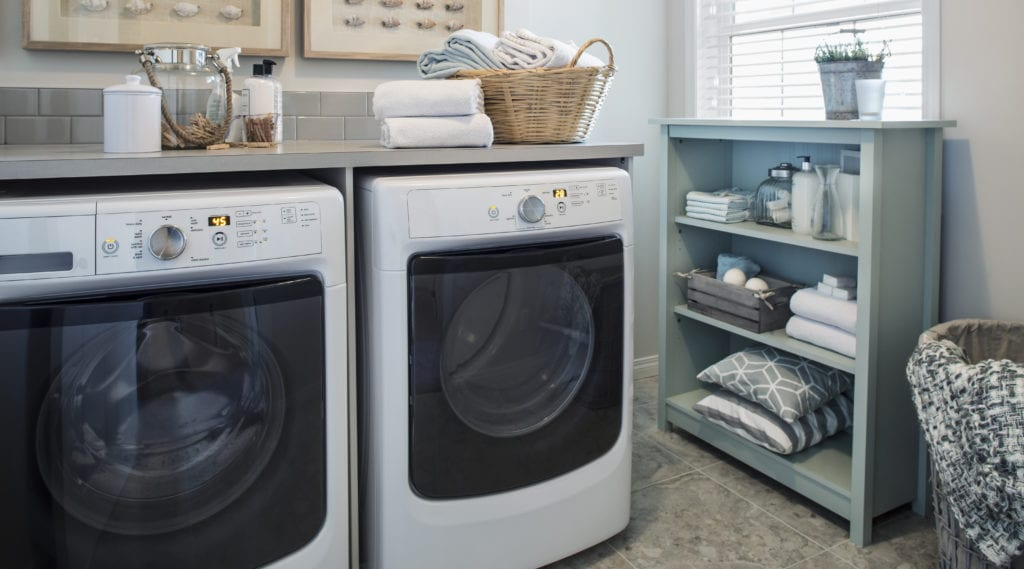 A brand new washer and dryer in a very organized laundry room.