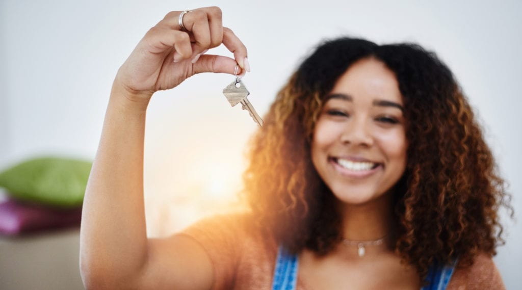 Young woman smiling and holding the keys to her first apartment.