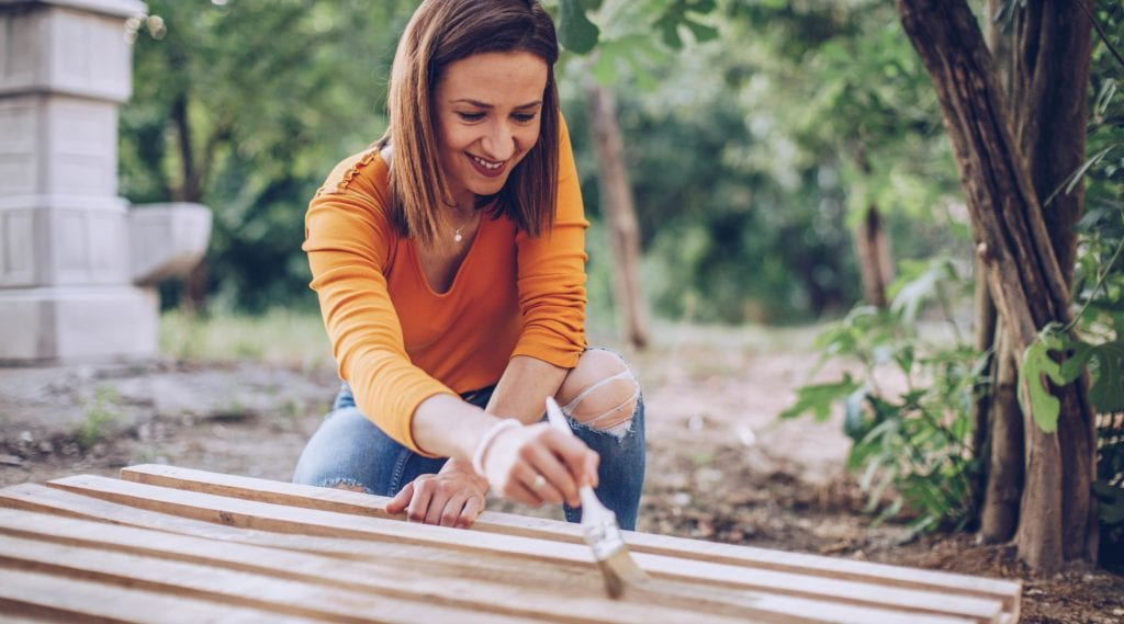 A woman paints a wooden pallet white as part of her DIY outdoor project.
