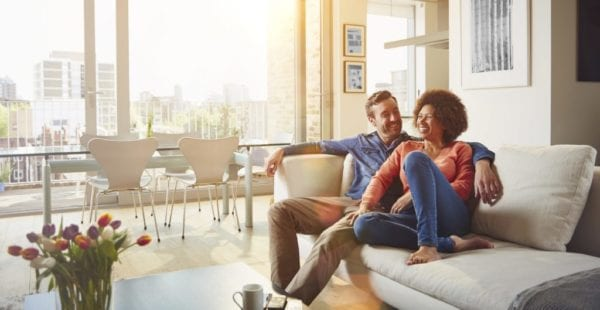 Couple sitting on couch of rented apartment