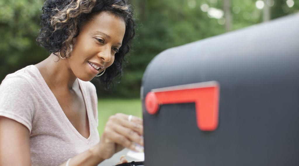 Woman takes her mail from her mailbox at her new home after successfully changing her address with USPS.