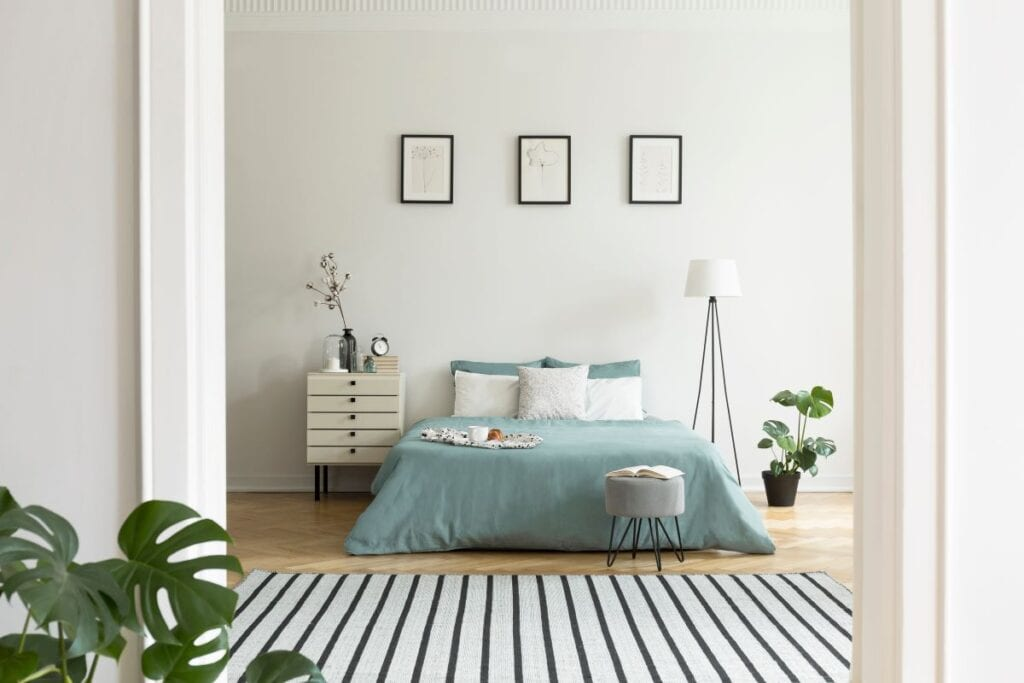 Bedroom with pastel comforter and striped area rug