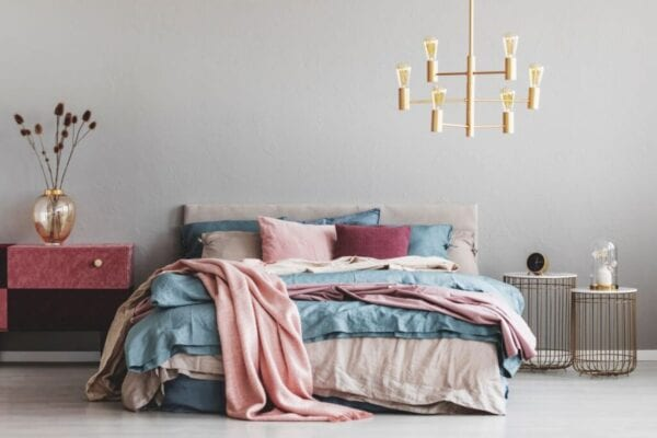 Bedroom with chandelier and blue, beige, and pink accents