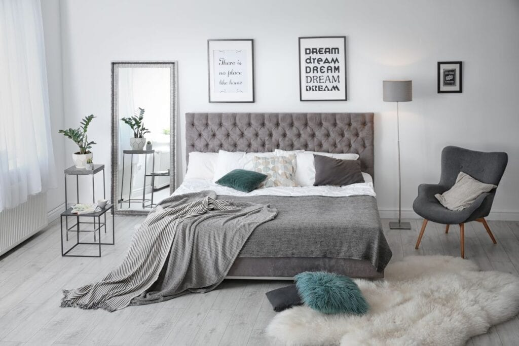 Modern bedroom with gray bed and tall standing mirror