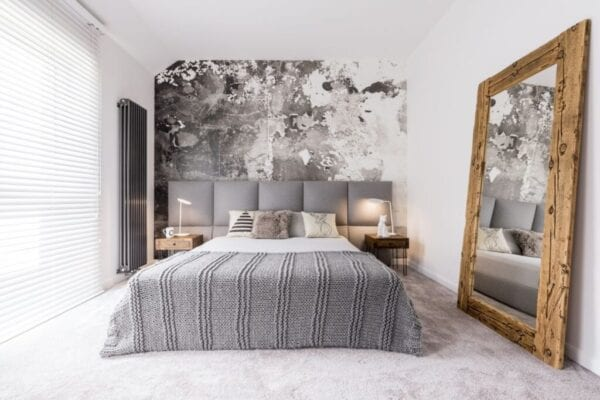 Small bedroom with bold wallpaper and large mirror