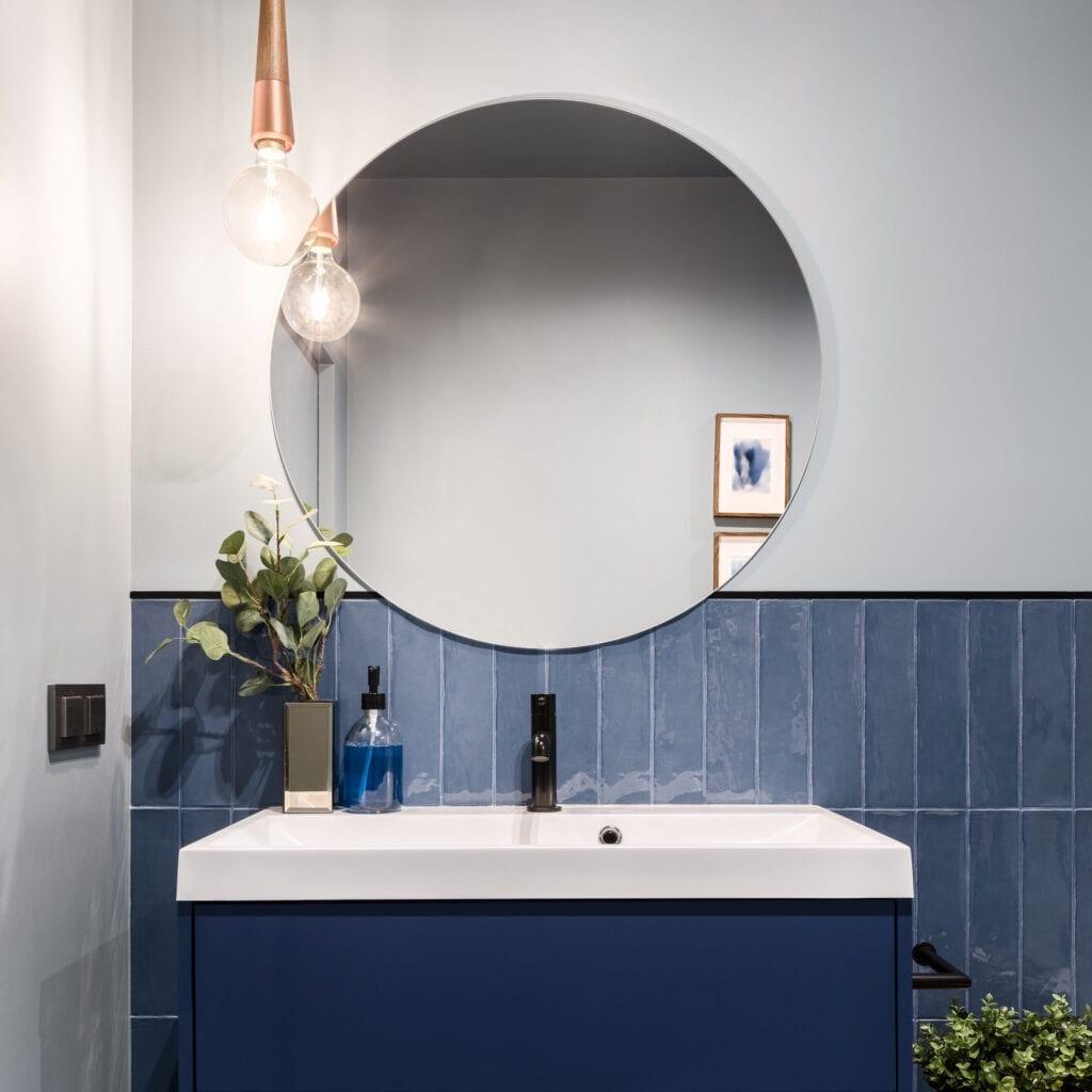 Salle de bain conçue avec une armoire bleue élégante, des carreaux de mur bleus et un grand miroir rond
