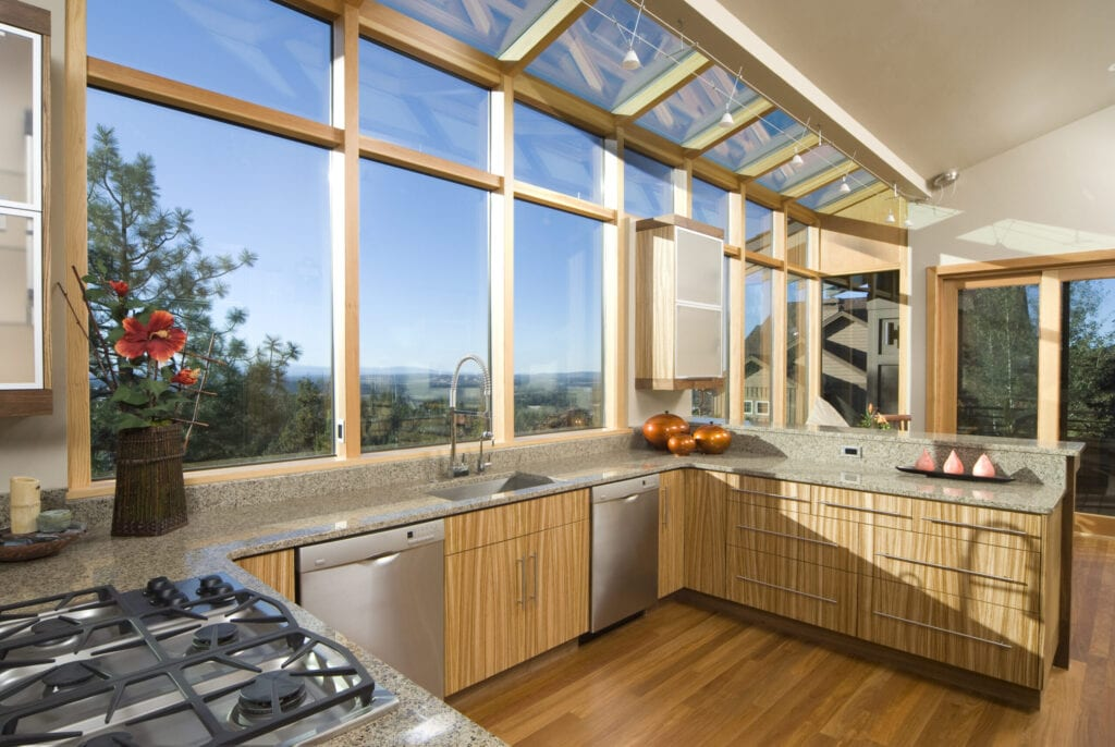 This modern asian style kitchen has many windows, with bamboo cabinets and floors.