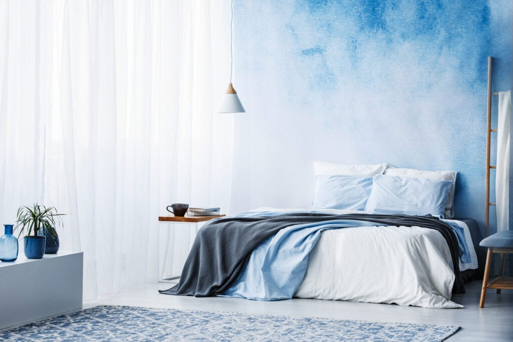 Plant on white cupboard in spacious blue bedroom interior with grey blanket on bed