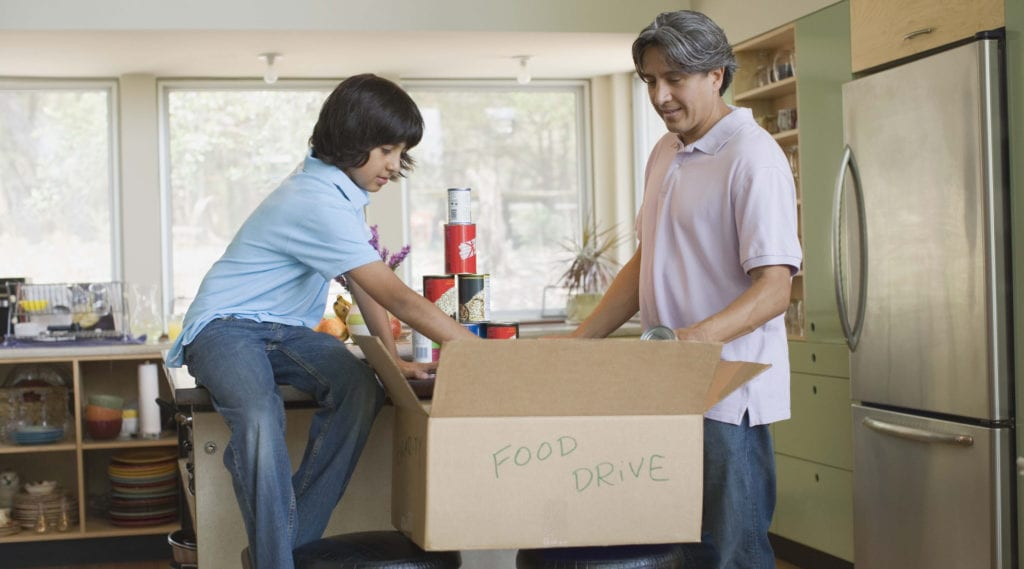 Father and son pack canned goods into a moving box labeled