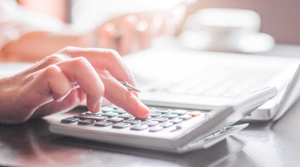A woman calculates her monthly home payments using a mortgage calculator.