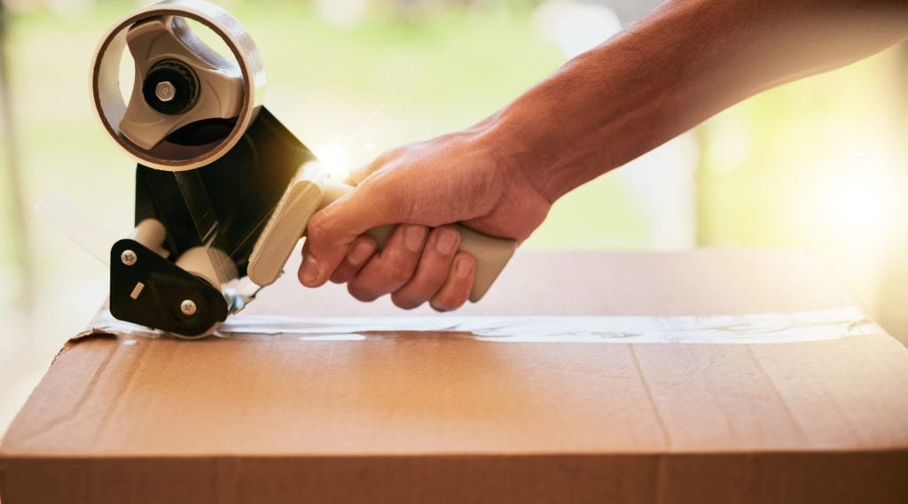 Closeup shot of a hand closing a cardboard box with tape during a move.