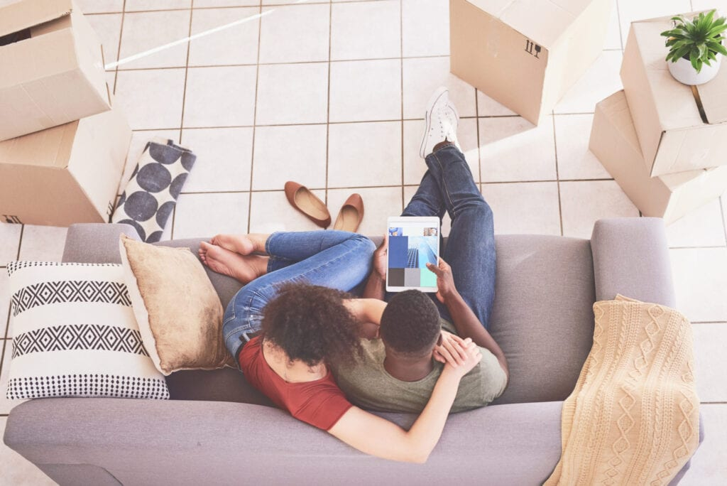 Young couple relaxing on couch and using a virtual room planner app