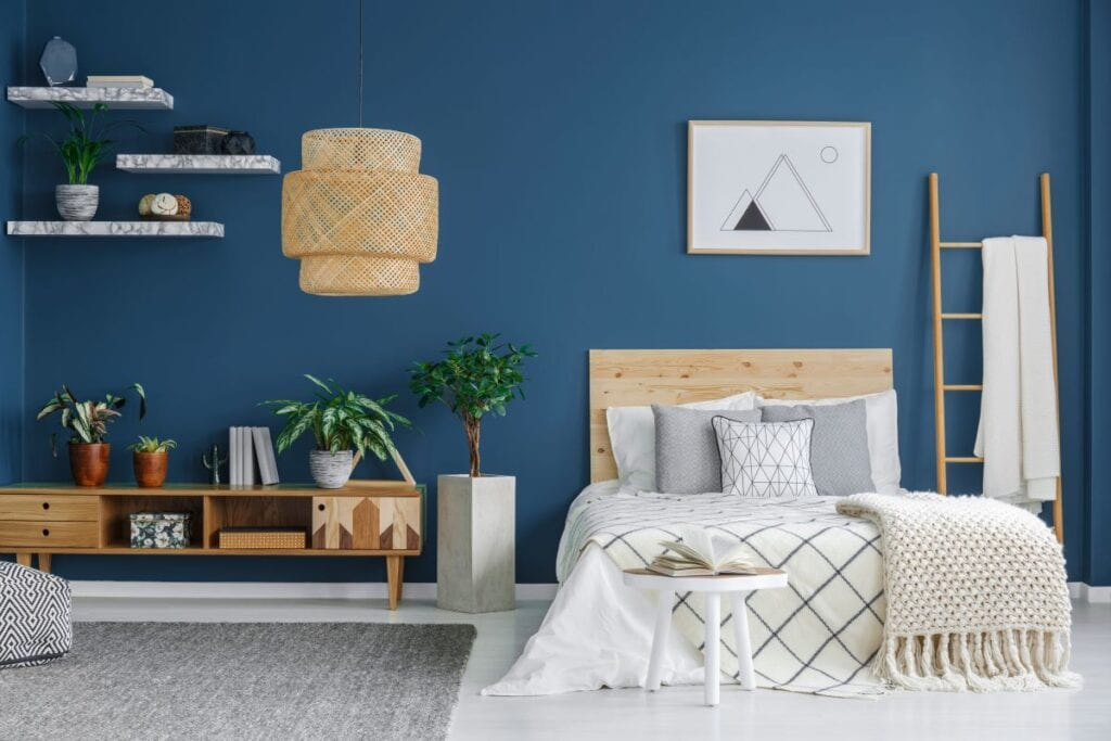 Bedroom with dark blue wall and floating shelves
