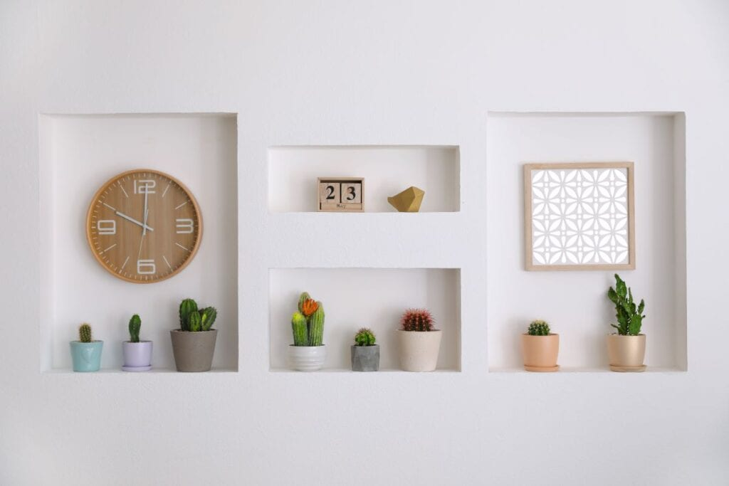 Potted cacti, clock, and picture frame in wall niches