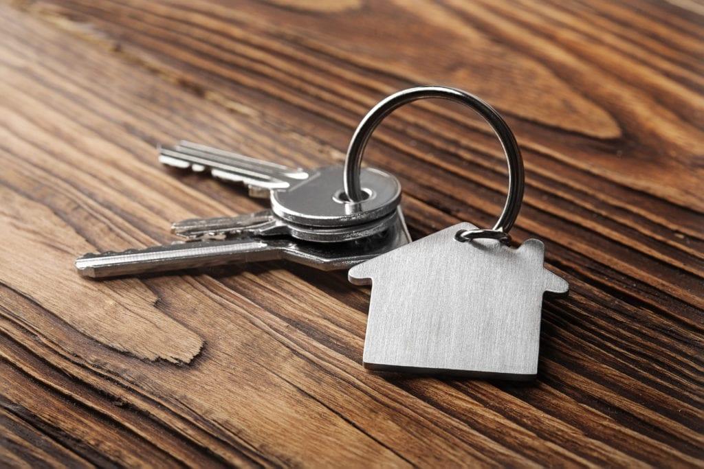 House key with house keychain on wood background