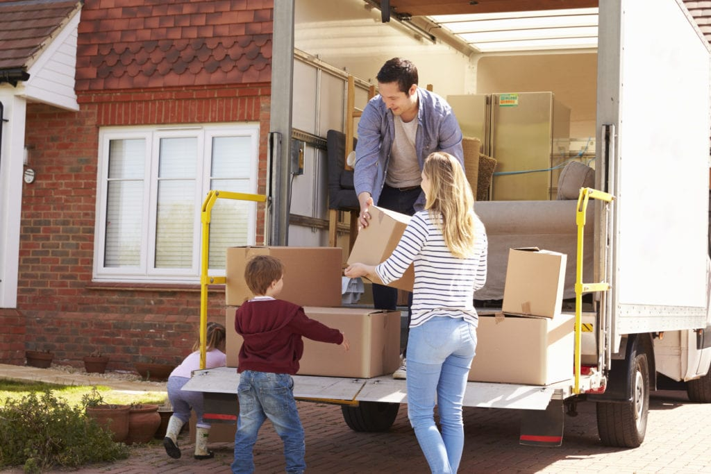 family of 3 packing a moving truck with boxes
