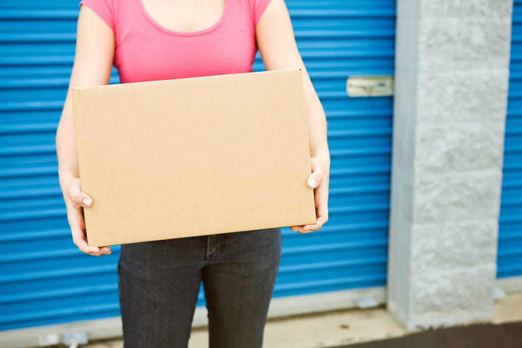 woman holds box in front of self storage unit