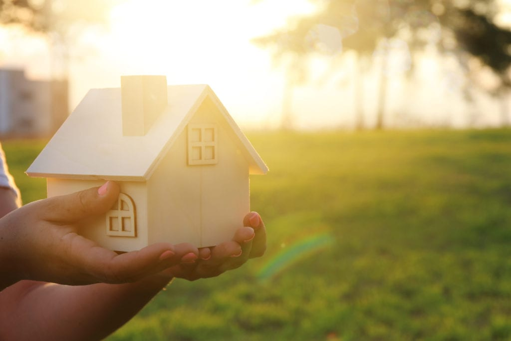 hands holding wooden house in grass field