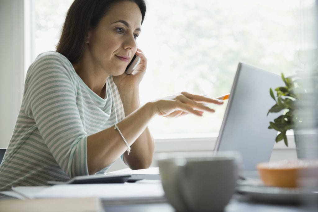 Woman using smartphone and laptop at home