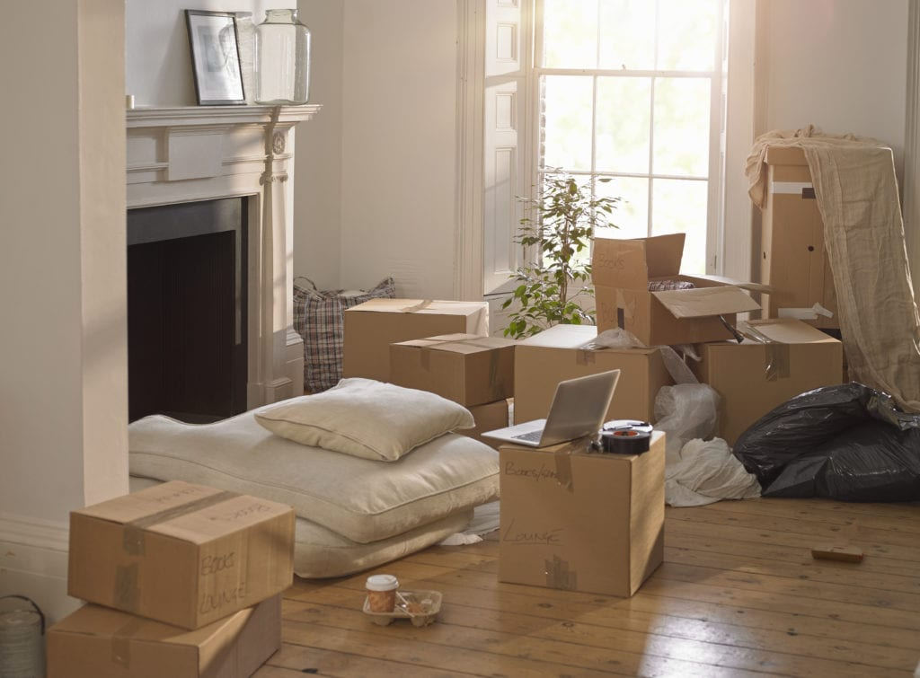 A room full of packing boxes and junk and a laptop