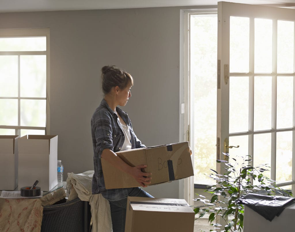 A woman carrying moving boxes at home